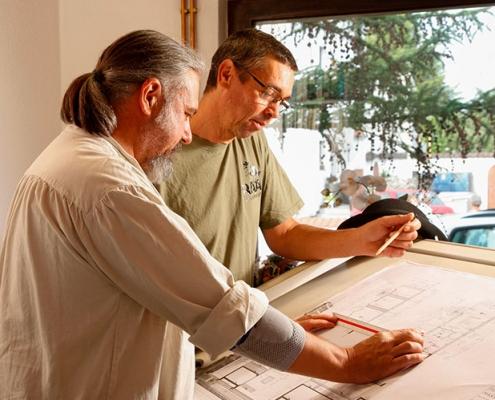 immerermeister Thorsten Raab und sein Mitarbeiter vor einem Bauplan für die Sanierung eines Fachwerkhauses