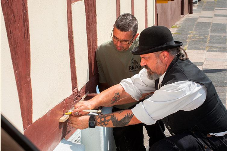 Restaurator Thorsten Raab und sein Mitarbeiter besprechen ein Projekt vor einem Fachwerkhaus