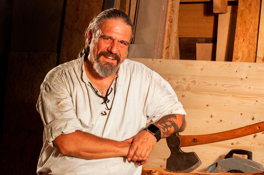 Zimmerer- und Dachdeckermeister und geprüfter Restaurator Thorsten Raab mit seinem Lieblings-Werkstoff Holz und Axt