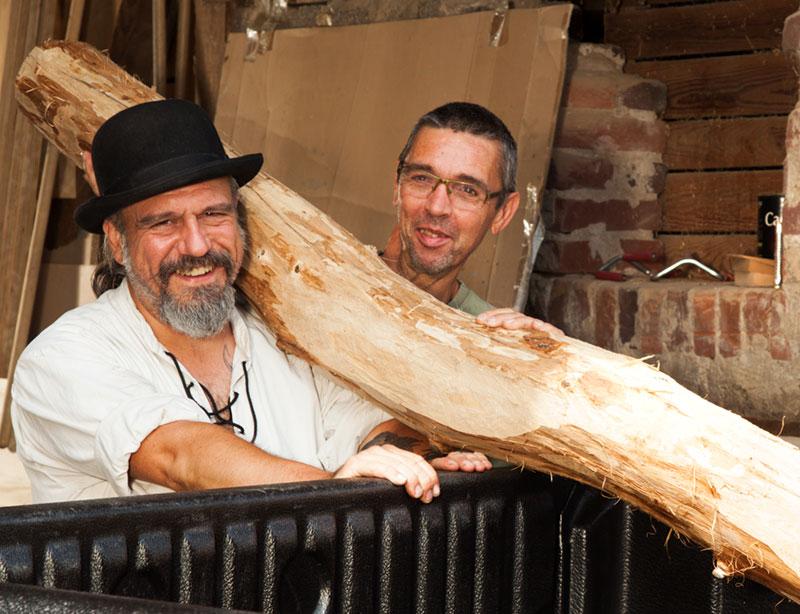 Betriebsinhaber Thorsten Raab und sein Altgeselle mit einem geschälten Baumstamm