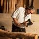 Thorsten Raab bearbeitet in seiner Werkstatt einen Holzstamm mit einer Axt