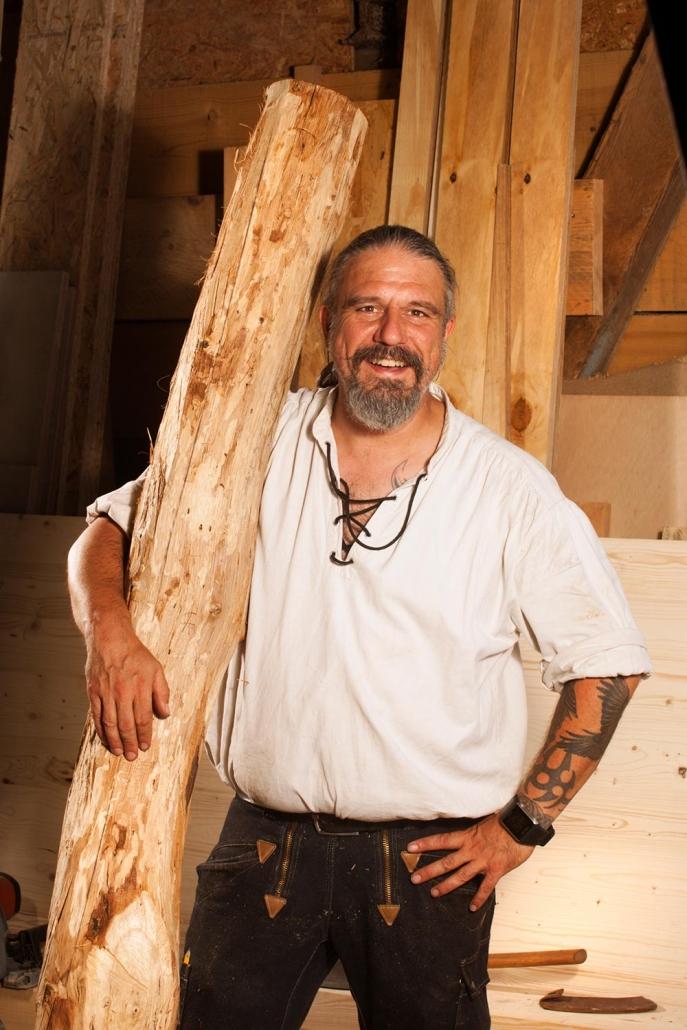 Zimmerer Thorsten Raab hält einen geschälten Baumstamm in seiner Werkstatt