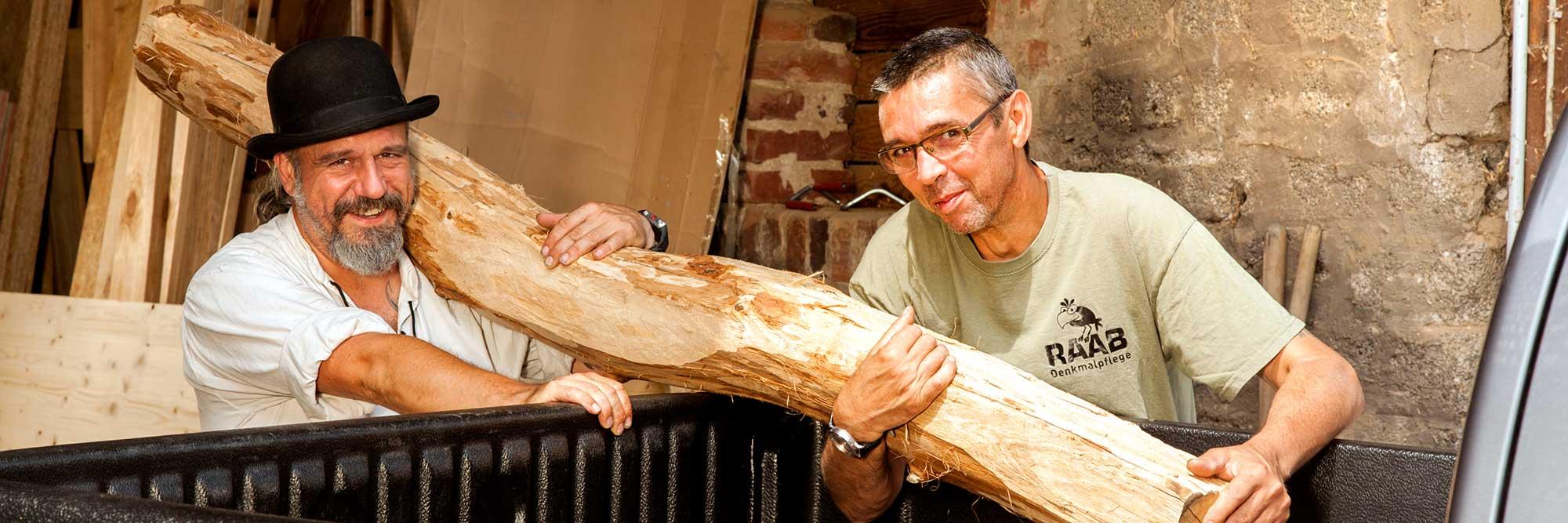 Betriebsinhaber Thorsten Raab und sein Altgeselle halten einen geschälten Baumstamm