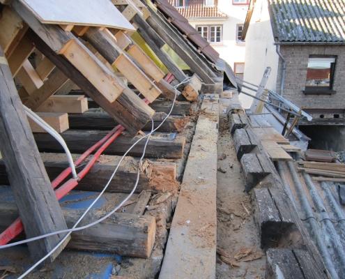 zurückgeschnittene Fußpunkte der Balken eines sanierungsbedürftigen Dachstuhls