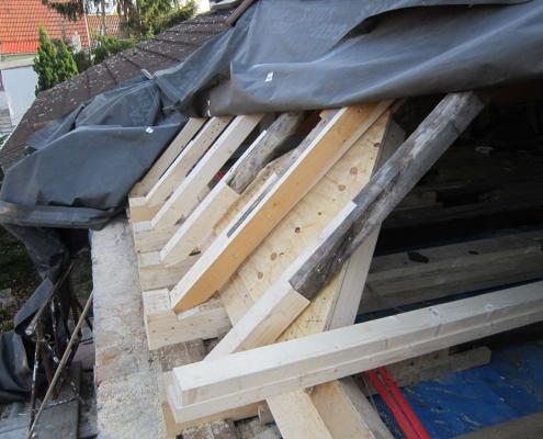 Dachstuhl eines renovierungsbedürftigen Daches mit bereits ergänzten, gesundgeschnittenen Bauteilen