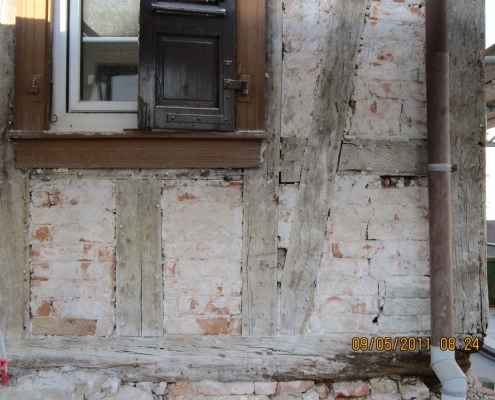 Fachwerkhaus mit abgeschlagenem Putz und schadhaften Fachwerkbalken aus Eichenholz