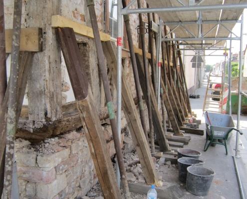 die Mauern eines Fachwerkhaues, das gerade restauriert wird, sind mit Holzbalken abgestützt