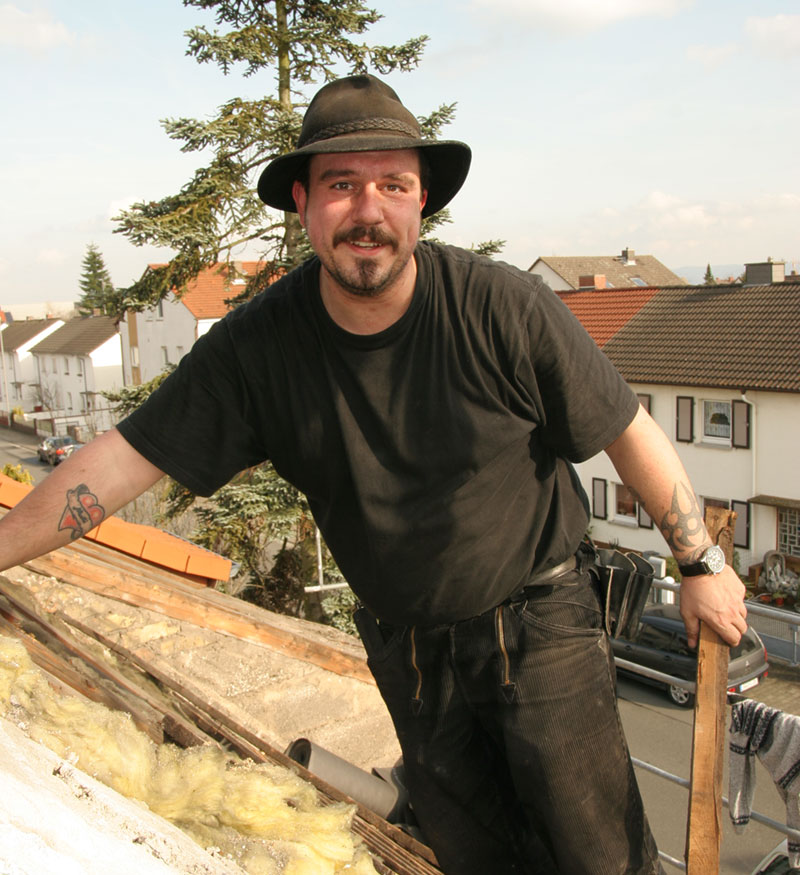 Dachdecker- und Zimmerermeister bei einer Dachsanierung auf dem Dach
