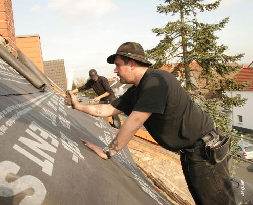 Dachdecker auf dem Dach während einer Dachumdeckung