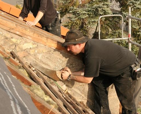 Dachdeckermeister schneidet mit der Säge auf dem Dach einen Balken zurecht