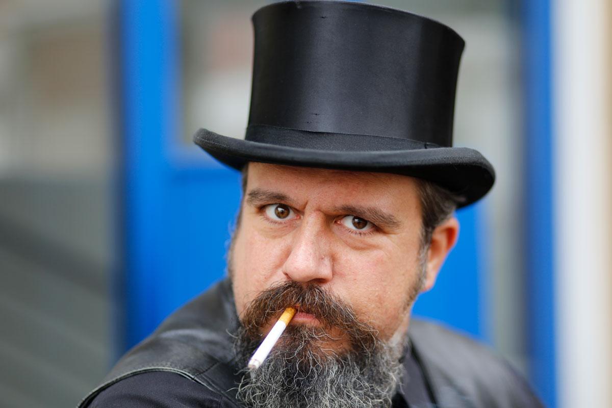Thorsten Raab mit schwarzem Zylinder und Zigarette im Mund