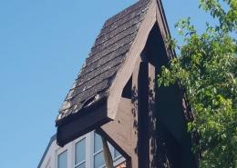 Ein Holzkreuz neben einem Baum vor blauem Himmel mit marodem Holzdach