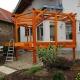 überdachte Veranda aus lasiertem Holz mit Dachwerk und Treppenaufgang beim Aufbau im Garten des Kunden