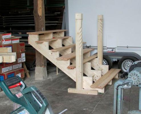 vormontierte, aufgesattelte Treppe zur Veranda mit geschnitzten Pfosten als Rohbau in der Werkstatt