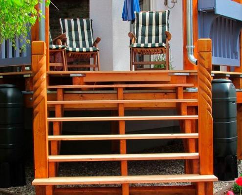 Treppe vom Garten zur Veranda aus lasiertem Holz mit Schnitzdetails