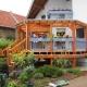 runde Holzveranda mit Treppenaufgang in lasiertem Holz mit blauem Geländer