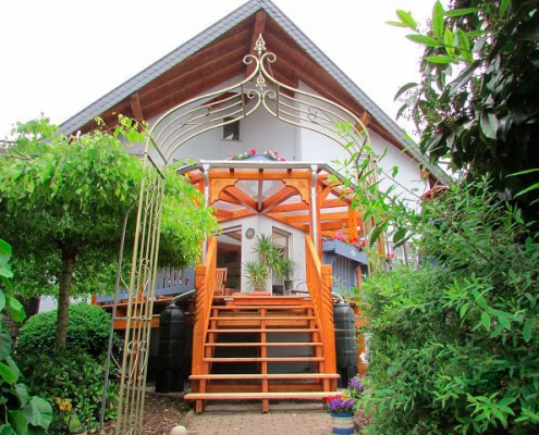 grün bewachsender Garten mit Ziertor und Holzveranda mit Treppenaufgang