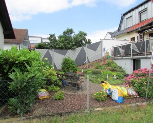 Ein Garten mit auf Umgebung abgestimmten Sichtschutzzaun und neuer Bepflanzung