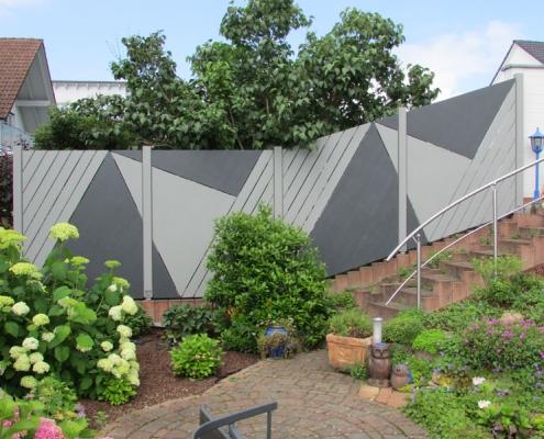 ein moderner, hölzerner, dunkel- und hellgrau grafisch gemusterter Sichtschutzzaun im Garten