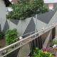 Moderner Sichtschutzzaun mit dunkel- und hellgrauem Holz passend zum Design des Treppengeländers